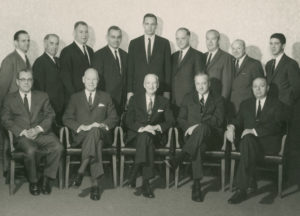 A.G.Becker & Co., Inc.  Board of Directors, Late 1965.  Seated, left to right: Vince Flett, Bill Mabie, James Becker, Paul Judy, Irv Sherman; standing, left to right: Roger Brown, Herb Schaffner, Mac Skall, Jack Connor, Jim Lewis, Harry Weber, Don Pearson, Maury Cann, and Dave Heller.